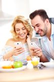 Happy couple eating breakfast and using smart phone Royalty Free Stock Image