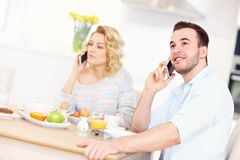 Happy couple eating breakfast and using smart phone Stock Photo