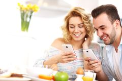 Happy couple eating breakfast and using smart phone Stock Image