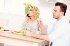 Happy couple eating breakfast and using smart phone Royalty Free Stock Images