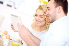 Happy couple eating breakfast and using tablet Royalty Free Stock Photo