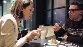 Happy couple eating cake for dessert at cafe stock video footage