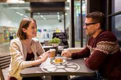 Happy couple eating cake for dessert at cafe. Food, people and dating concept - happy couple eating peace of cake or pie for dessert at cafe Royalty Free Stock Image
