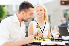 Happy couple eating dinner at restaurant terrace Royalty Free Stock Photos
