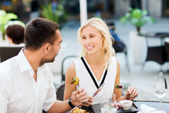 Happy couple eating dinner at restaurant terrace Royalty Free Stock Images