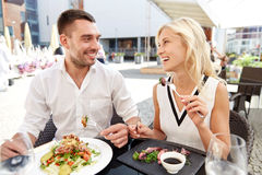 Happy couple eating dinner at restaurant terrace. Love, date, people, holidays and relations concept - happy couple eating salad for dinner at cafe or restaurant royalty free stock photo