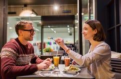 Happy couple eating dinner at vegan restaurant Stock Image