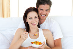 Happy couple eating fruits lying on their bed Royalty Free Stock Photo