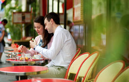 Happy couple eating macaroons in a cafe Royalty Free Stock Photography