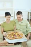 Happy couple eating pizza Stock Photography