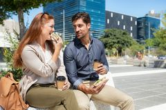 Happy couple eating sandwich at city square royalty free stock photography