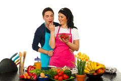 Happy couple eating strawberry in kitchen. Happy women giving to her husband to eat strawberry in their kitchen against white background Royalty Free Stock Photography