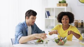Happy couple eating vegetable salad at home stock footage