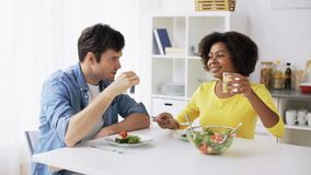 Happy couple eating vegetable salad at home stock video footage