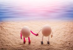 Happy couple of eggs hold hands on a sandy beach royalty free stock photos