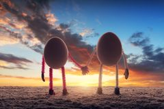 Happy couple of eggs on the sandy beach. Against colorful sunset background Royalty Free Stock Images