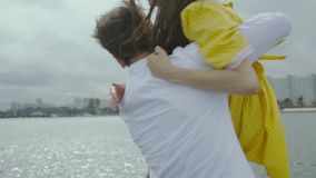 Happy couple at the embankment. Man picking up on hands her girlfriend. And after they starting dancing. Slow motion stock footage