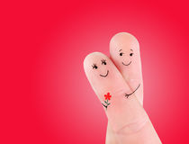Happy couple embrace with flower concept, painted at fingers. Against red background royalty free stock image