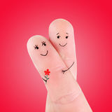 Happy couple embrace with flower concept, painted at fingers. Against red background royalty free stock photos