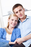 Happy couple embraces each other on the sofa Royalty Free Stock Photos