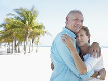 Happy Couple Embracing On Beach Royalty Free Stock Photography