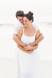 Happy couple embracing on the beach Stock Image