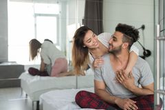 Happy Couple Embracing In Bed, Young Man And Woman Smiling Sit In Bedroom Hugging And Looking At Each Other. Love And Relationship Concept stock photography