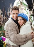 Happy Couple Embracing At Christmas Store Stock Photography