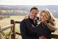 Happy couple embracing in the countryside look to camera Stock Image