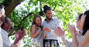 Happy couple embracing while friends applauding during lunch stock footage