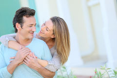 Happy couple embracing in front of their home Stock Photography