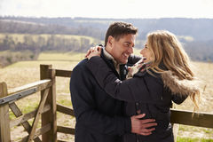 Happy couple embracing by a gate in the countryside Royalty Free Stock Photo