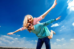 Happy couple embracing and having piggyback ride under the blue. Sky Royalty Free Stock Images