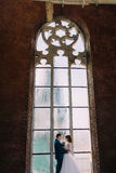 Happy couple embracing holding arms in the front of old Gothic window Stock Photos