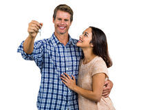 Happy couple embracing while holding home keys Stock Photo