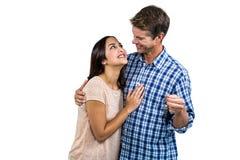 Happy couple embracing while holding keys Royalty Free Stock Image