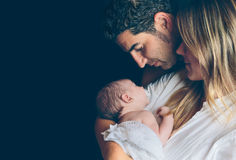 Happy couple embracing and looking newborn over Royalty Free Stock Photo