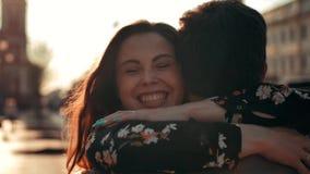 Charming brunette woman running to hug her boyfriend at urban street.