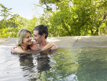 Happy Couple Embracing In Pool. Happy adult couple embracing in swimming pool against trees Royalty Free Stock Photography