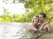 Happy Couple Embracing In Pool. Smiling adult couple embracing in swimming pool against trees Royalty Free Stock Photo
