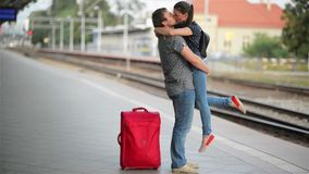 Happy couple embracing on railway station platform. Farewell at the train station, girl and guy kissing on the platform stock video