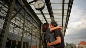 Happy couple embracing on railway station platform. Farewell at the train station, young girl and guy kissing on stock footage