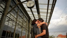 Happy couple embracing on railway station platform. Farewell at the train station, young girl and guy talking on stock video footage