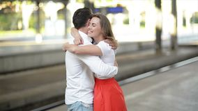 Happy Couple Embracing On Railway Station Platform. Farewell At The Train Station, Young Girl And Guy Are Hugging On. Platform. HD, Together, Good Mood stock video footage