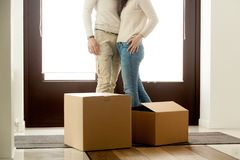 Happy couple embracing standing near boxes on moving day, close. Happy couple embracing standing near cardboard boxes on moving day, homeowners renters tenants Stock Image