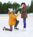 Happy couple with engagement ring on skating rink. Love, holidays and relationships concept - happy couple with engagement ring at outdoor skating rink royalty free stock photos