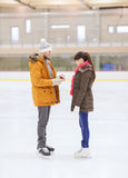 Happy couple with engagement ring on skating rink Royalty Free Stock Image