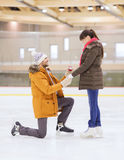 Happy couple with engagement ring on skating rink Royalty Free Stock Photo