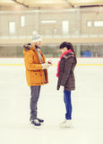 Happy couple with engagement ring on skating rink Stock Images