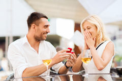 Happy couple with engagement ring and wine at cafe. Love, proposal, relations, people and holidays concept - happy couple with engagement ring in small red gift stock image